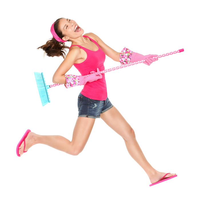 Cleaning woman jumping happy excited during spring cleaning fun. Funny energetic beautiful girl with cleaning broom playing air guitar isolated on white background. Multiracial white Caucasian / Chinese Asian female model.