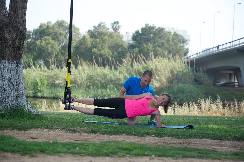 מאמן כושר אישי - תרגיל גשר צד בתליית רגליים על TRX